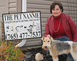 Betty with her dog standing in front of the Pet Nannie sign